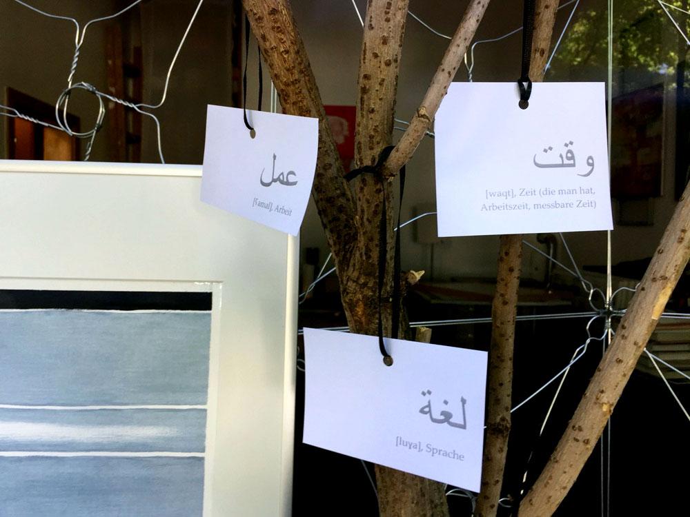 Zettel mit arabischen Schriftzeichen und Übersetzung, die auf Baum hängen